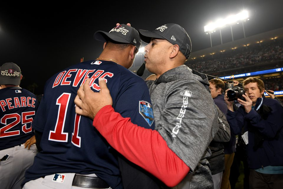 Rafael Devers talks with Alex Cora on the field at Dodger Stadium after winning the 2018 World Series. Cora believes Devers will be a much better hitter in 2019.