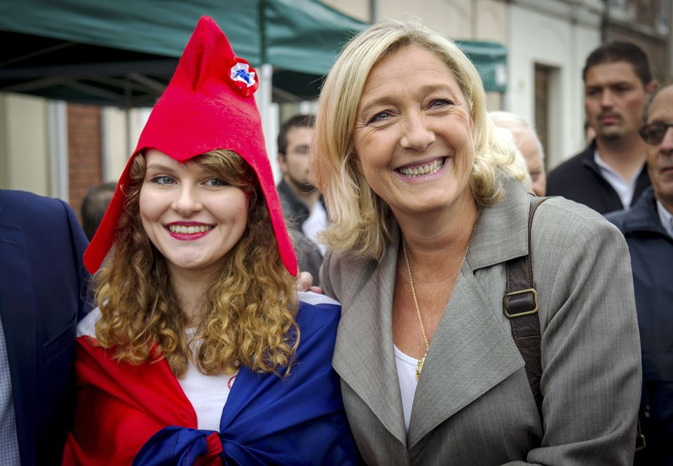 Marine Le Pen, president of the French far-right party National Front, poses beside a young girl dressed as Marianne, a personification of the French Republic, in northern France on Sept. 14.