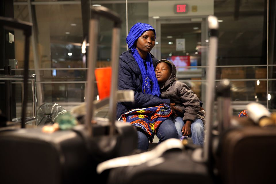 Vanisi Uzamukunda comforted her sleepy daughter, Sarah, 7, while waiting for their baggage at the Manchester–Boston Regional Airport in Manchester, N.H.