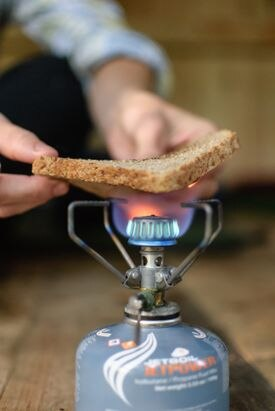 A hiker at the Old Hermit Shelter makes toast over an isobutane canister.