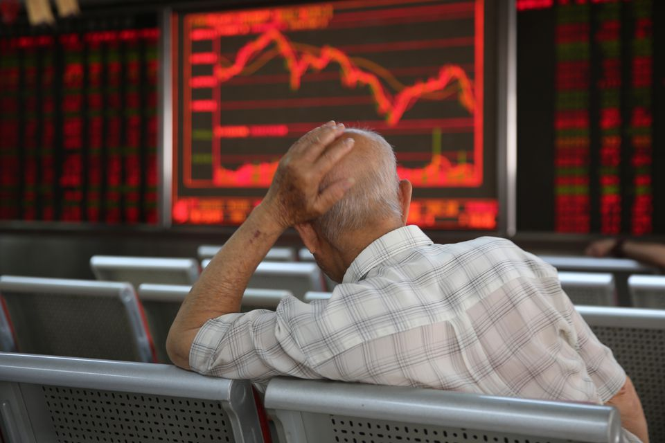A Chinese investor watches the stock index and prices in Beijing.