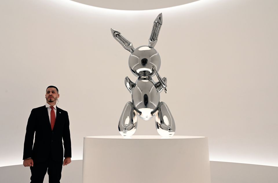 """A security guard stands next to Jeff Koons' """"Rabbit."""" The sculpture sold at auction at Christie's for $91.1 million, breaking the record for a work by a living artist."""