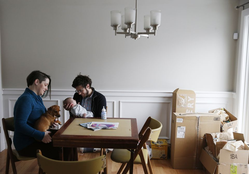 Phil Caminti and his wife, Ali Mercier sit with their four week old baby, Quinn, and their dog, Ada, in February inside the new home they just purchased in Lowell.