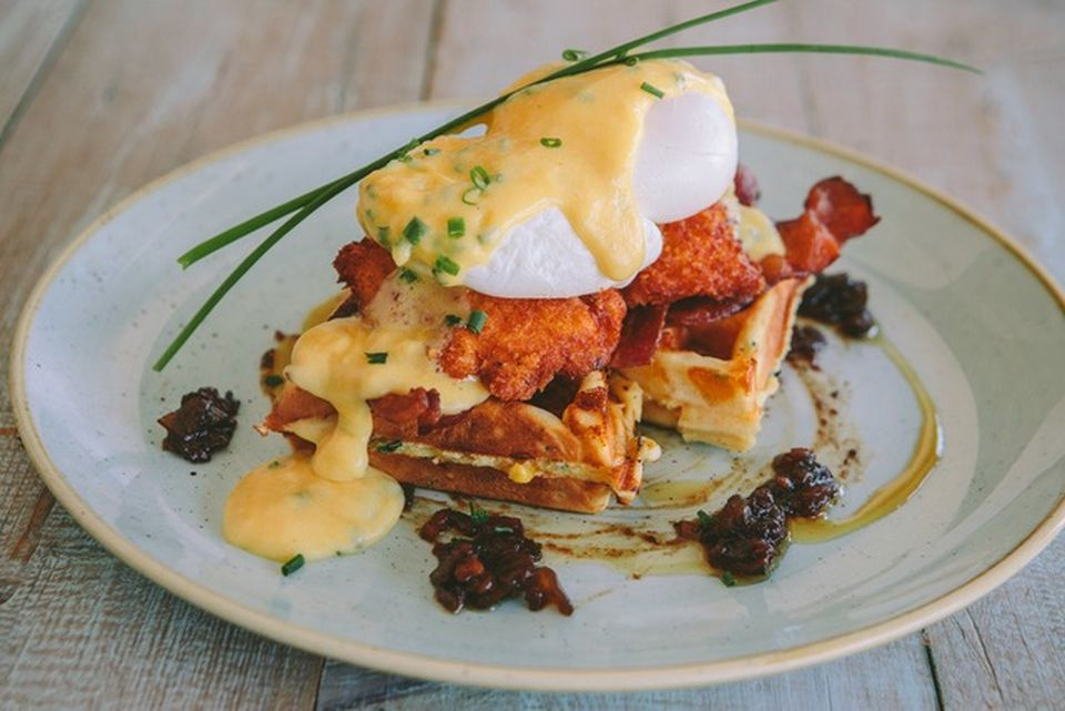 The chicken & waffle Benedict includes locally sourced eggs, maple syrup, chives, buttermilk, cheese, and butter.