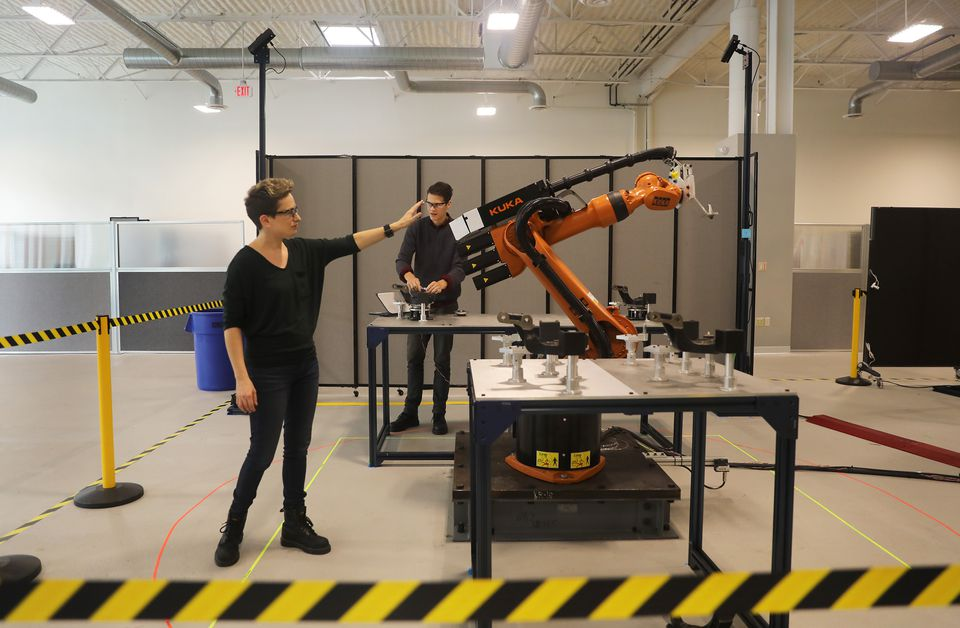 Clara Vu, of Veo Robotics Inc. in Waltham, showed how industrial robots can work with people. At rear is engineer Paul Schroeder.