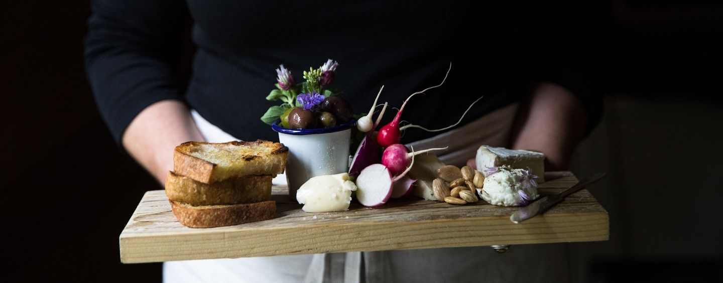 A cheese and bread board with olives, herbs, three cheese varieties, and fresh radishes and butter.