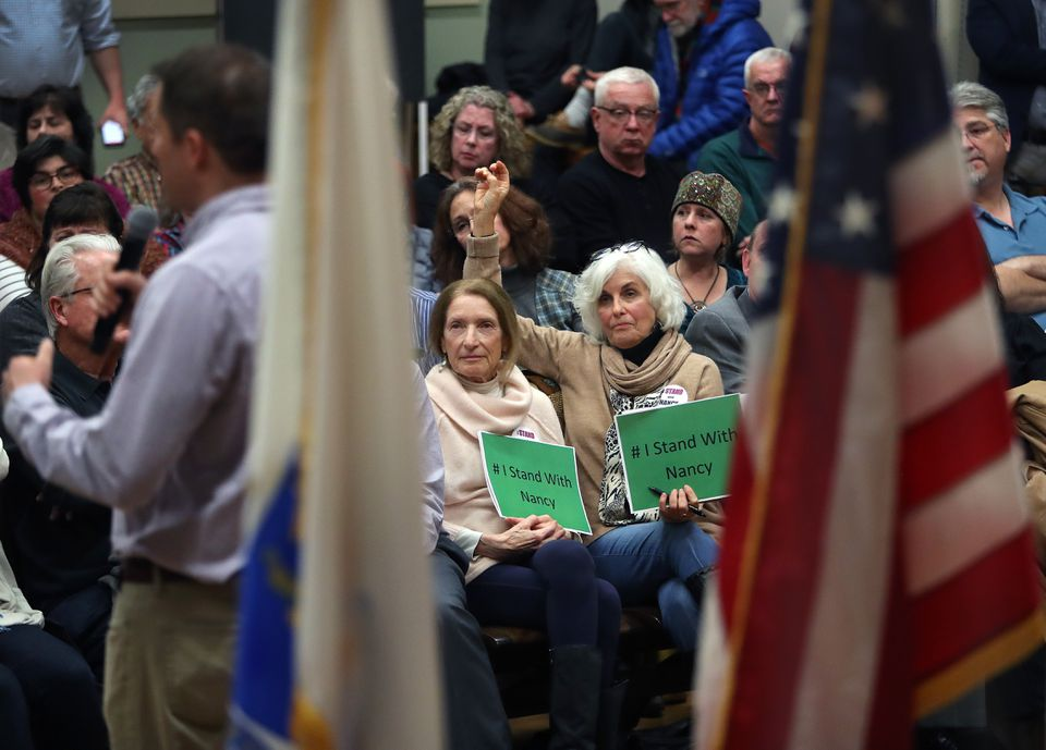 Some at US Representative Seth Moulton's town hall-style meeting in Amesbury Monday held signs backing Nancy Pelosi.