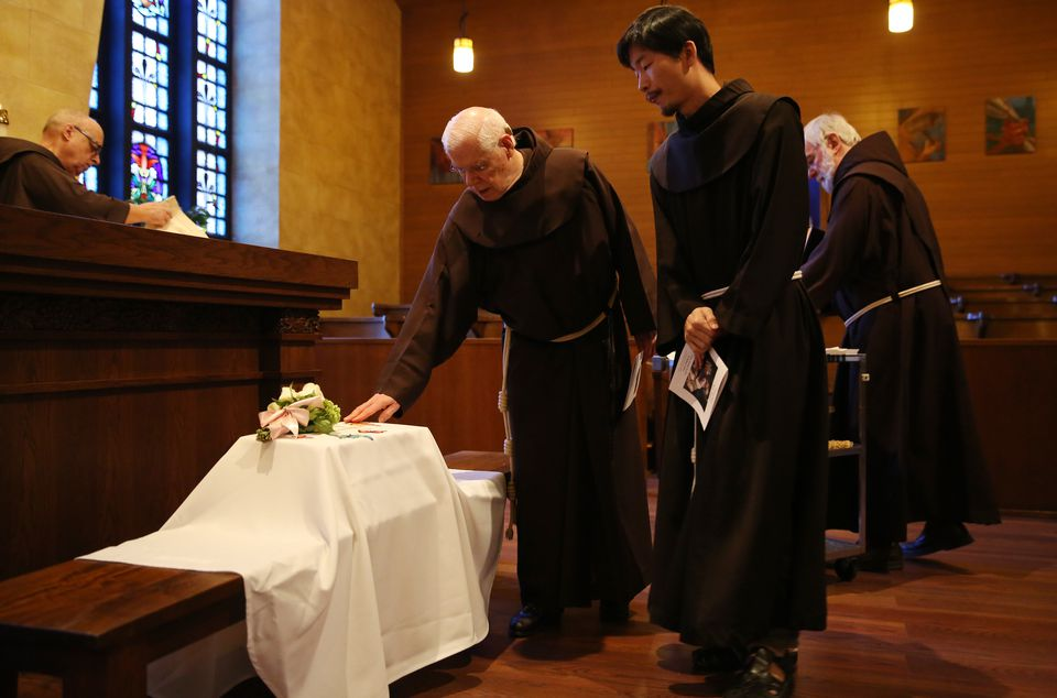 Franciscan Friars paused over over the baby's casket.