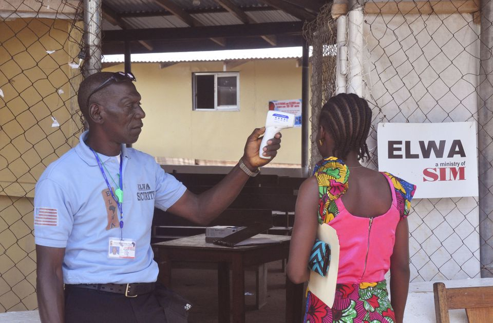 A family member of a boy, 10, who contracted Ebola in Liberia had her temperature taken at a clinic Friday.