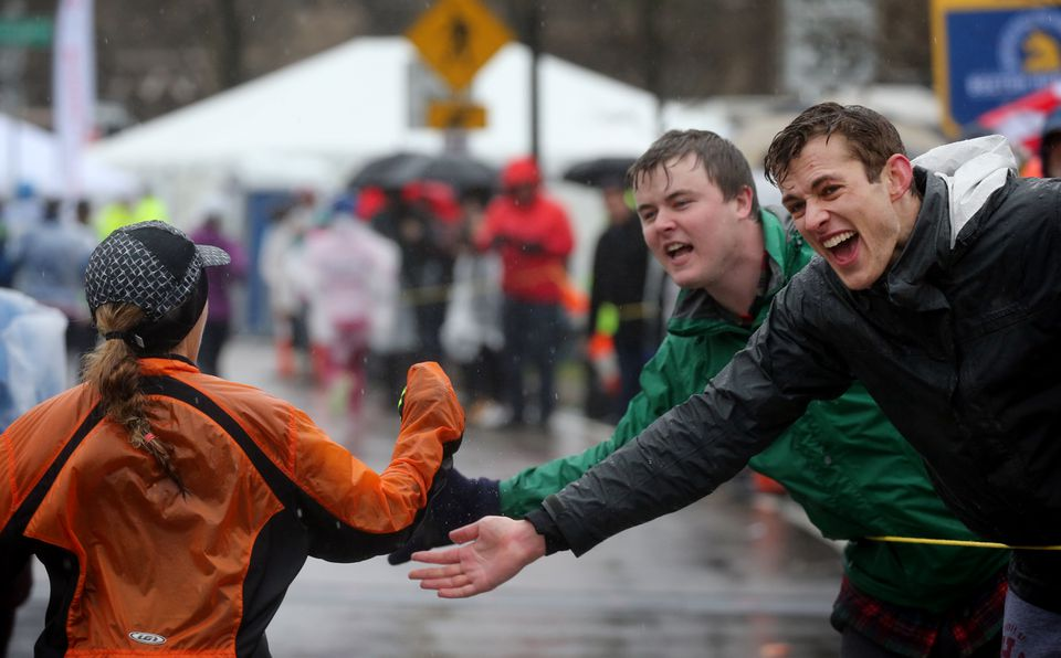 Bobby Looney (left) and Justin Mundt (right) offered a runner encouragement as they crested Heartbreak Hill during the 2018 Boston Marathon in Newton on April 16.