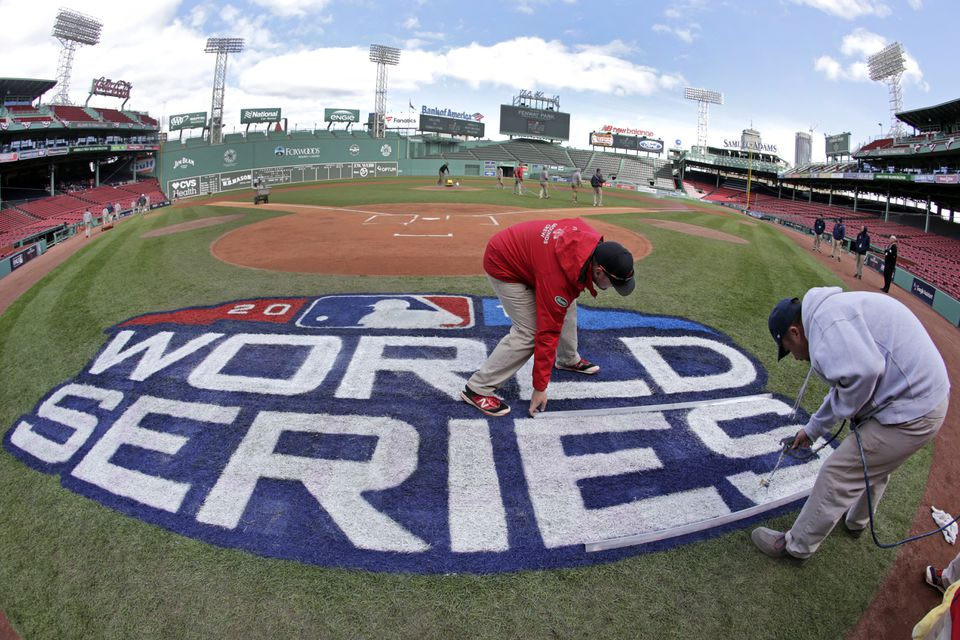 Grounds crew members paint the World Series logo behind home plate at Fenway Park, Sunday, Oct. 21, 2018, in Boston as they prepare for Game 1 of the baseball World Series between the Boston Red Sox and the Los Angeles Dodgers scheduled for Tuesday.