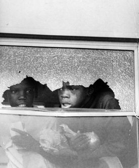 Boston students look out of a broken school bus window on Sept. 12. 1974.