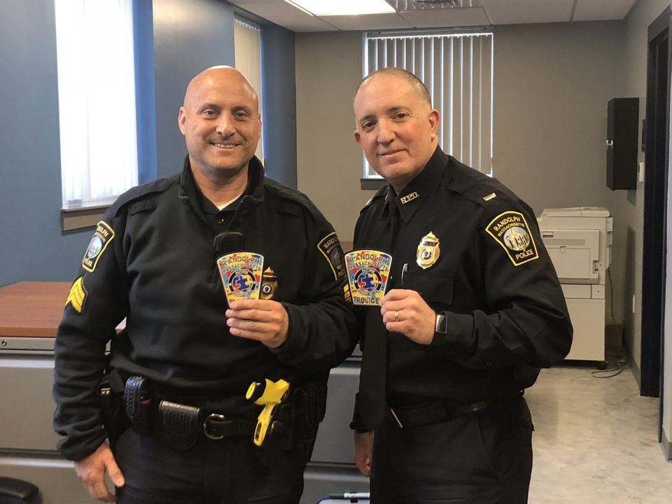 Randolph Police Sergeant Jason Fisher and Lieutenant Anthony Marag holding autism awareness patches, which the police department is selling throughout the month of April.