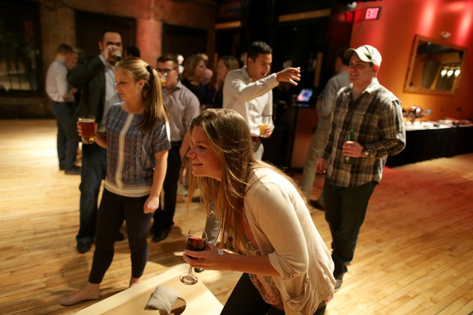 WinterWyman employees, including Jane Redden (center), enjoy a corporate cornhole fun event at Ned Devine's in Boston.