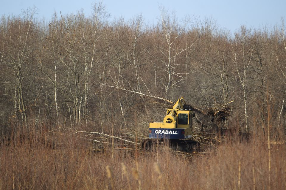"""Construction crews work to create a drainage area next to the area that will become the """"Winter Woods"""" neighborhood."""