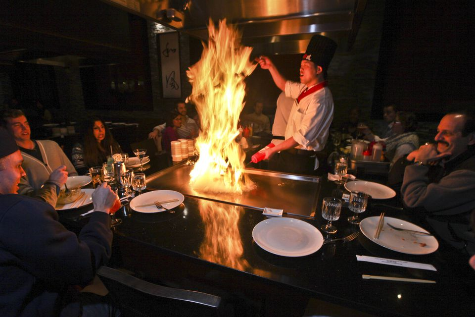 A  chef gets the grill going for diners at Osaka. Below (from left): the amazing roll and hibachi steak and shrimp.
