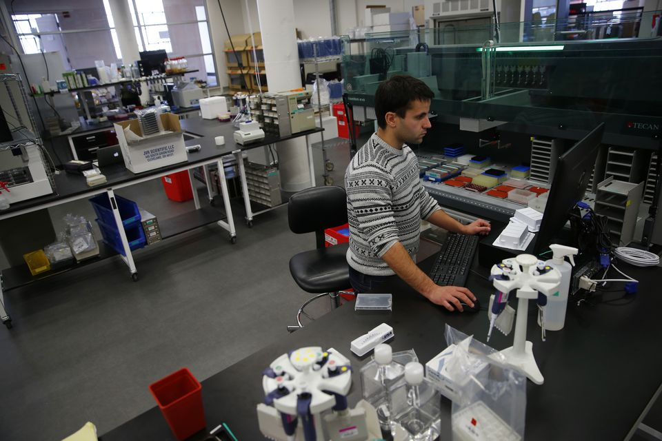 Build engineer Brian Carvalho, 24, of Cambridge, uses a liquid-handling robot to build DNA at Ginkgo Bioworks in South Boston.