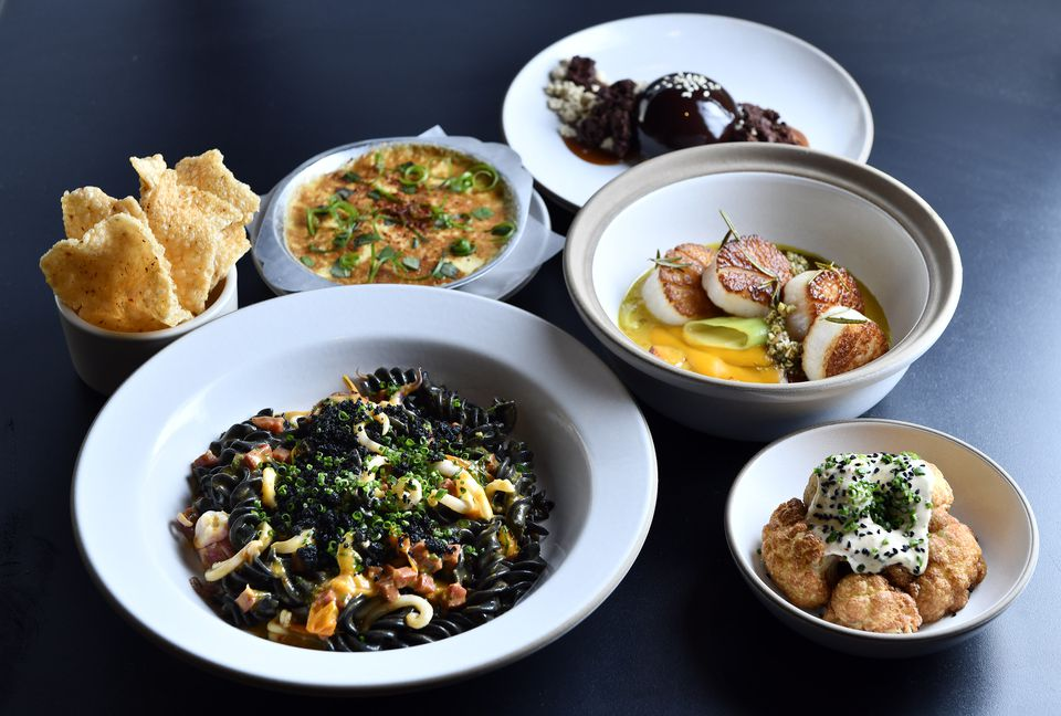 Clockwise from bottom left: Squid ink fusilli, crab gratin with puffed rice crackers, chocolate semifreddo, scallops, and fried cauliflower at Chickadee.