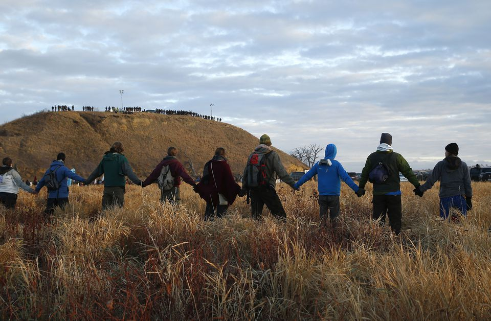 Protesters joined hands in prayer at the end of the day's protest as police lined the hill at Standing Rock.
