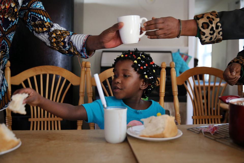 Sarah Bayavuge, 7, had a cup of porridge and bread with her family at their home in Lowell.