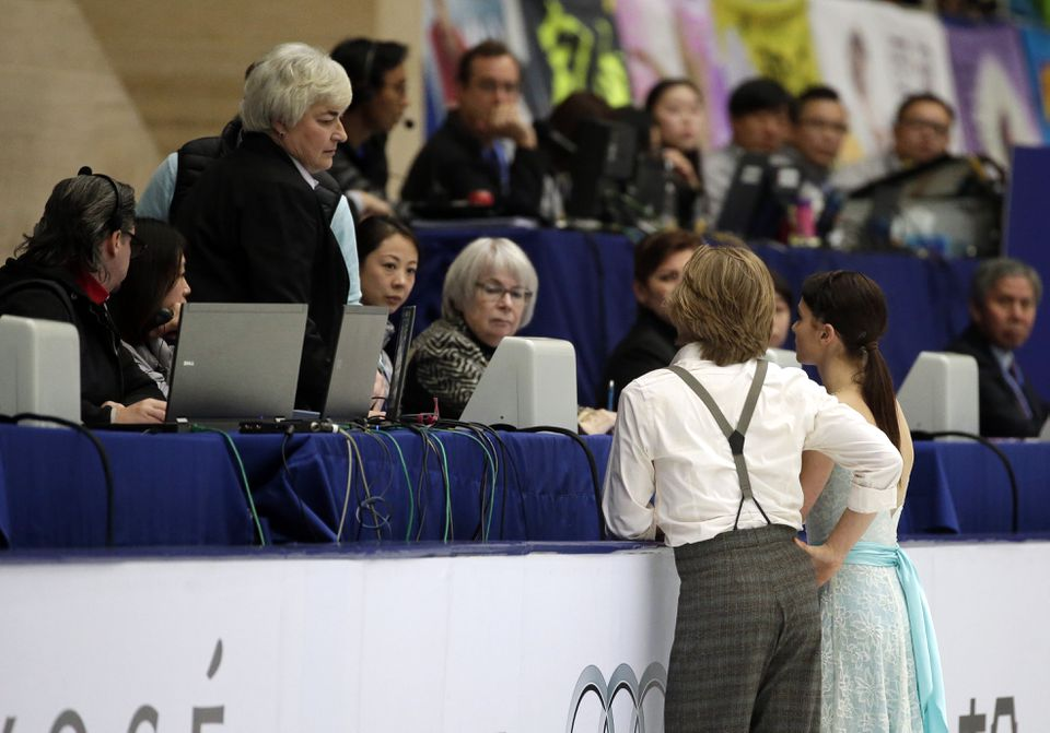 Kaitlin Hawayek and Jean-Luc Baker of the United States talk with the judges during the Grand Prix of Figure Skating in Beijing in November.