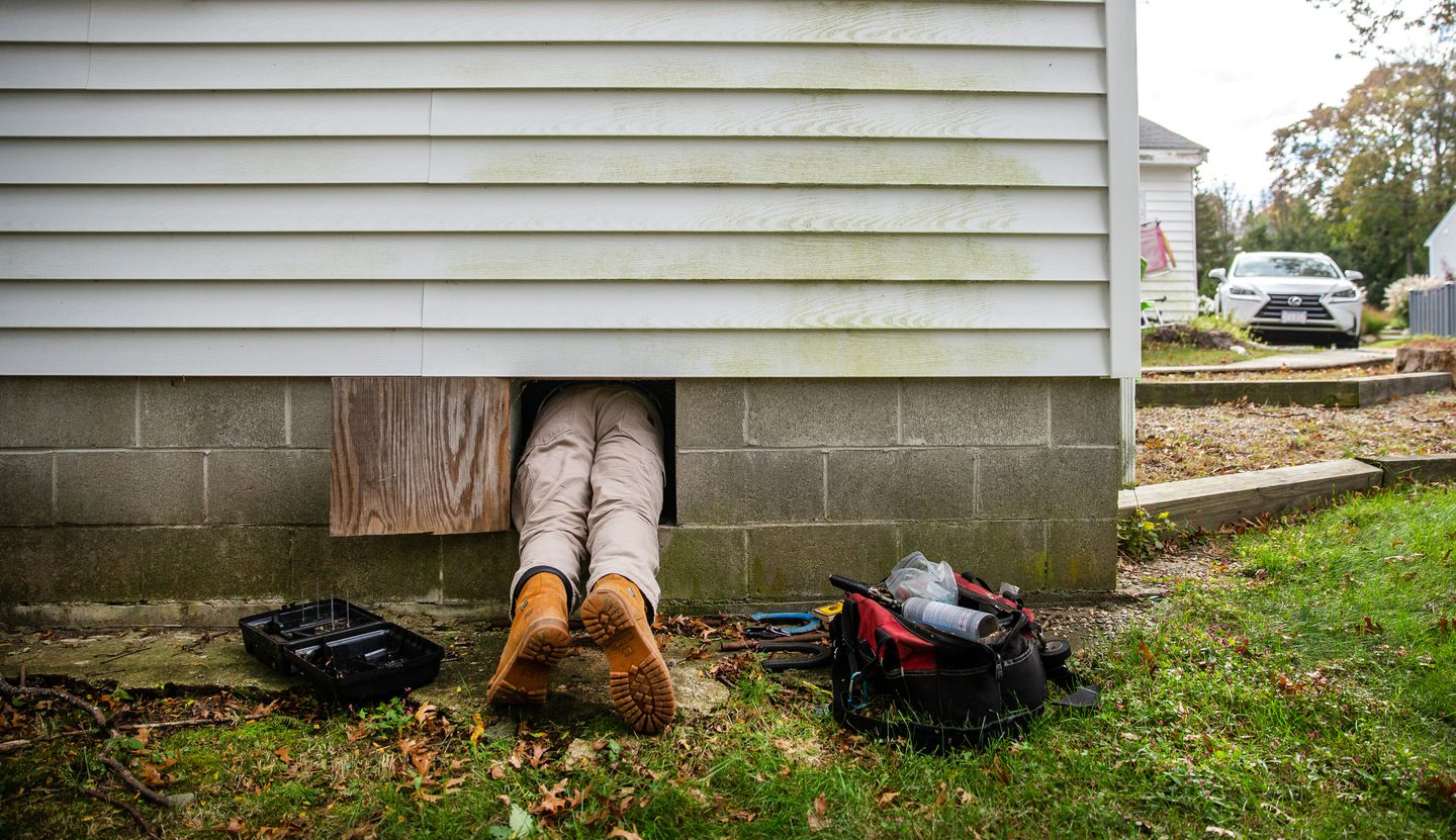 Rich Cyr of B&B Pest Control entered a crawl space to place rat traps at a home in Marblehead.