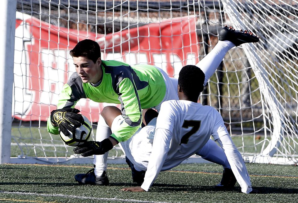 Wellesley keeper Ethan Liss-Roy makes a save over BC High's Osa Owens during the first half of the Division 1 South soccer final.