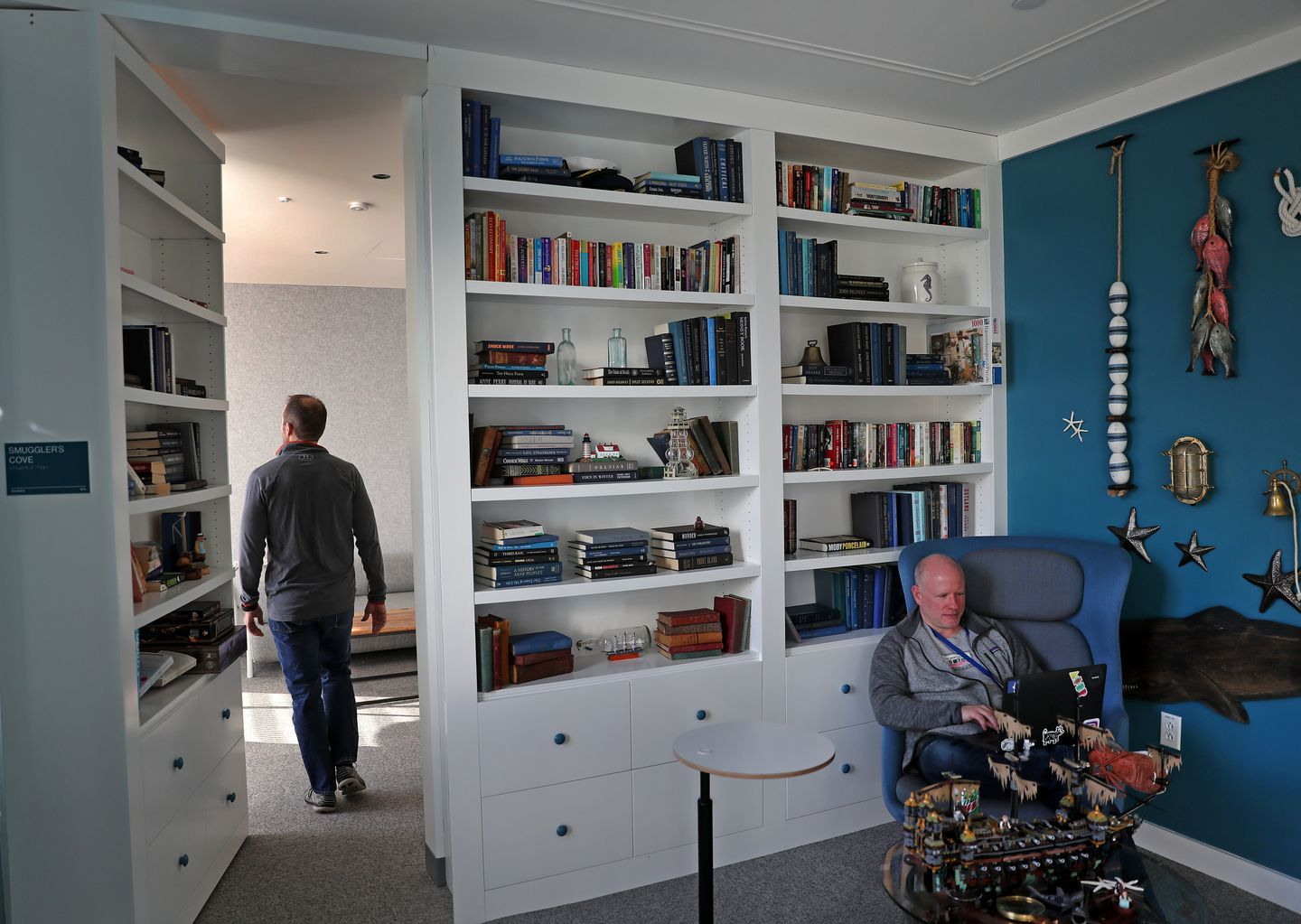 Facebook's library with a bookcase wall that opens into a private or quiet room in the Cambridge office.