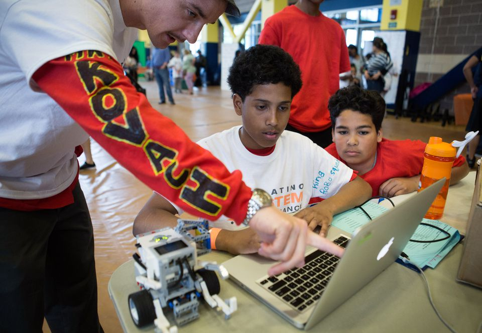 Science teacher Peter Kovach (left) assists students Nelfi Morales, 13, (center) and Taylor Garcia, 13, (right) during the Latino STEM Alliance's 2016 Annual Robotics Competition and Family Science Fair last month in Boston.