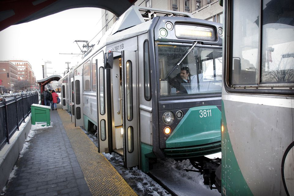 An MBTA employee sits in the drivers' seat of a Green Line car on Commonwealth Avenue,