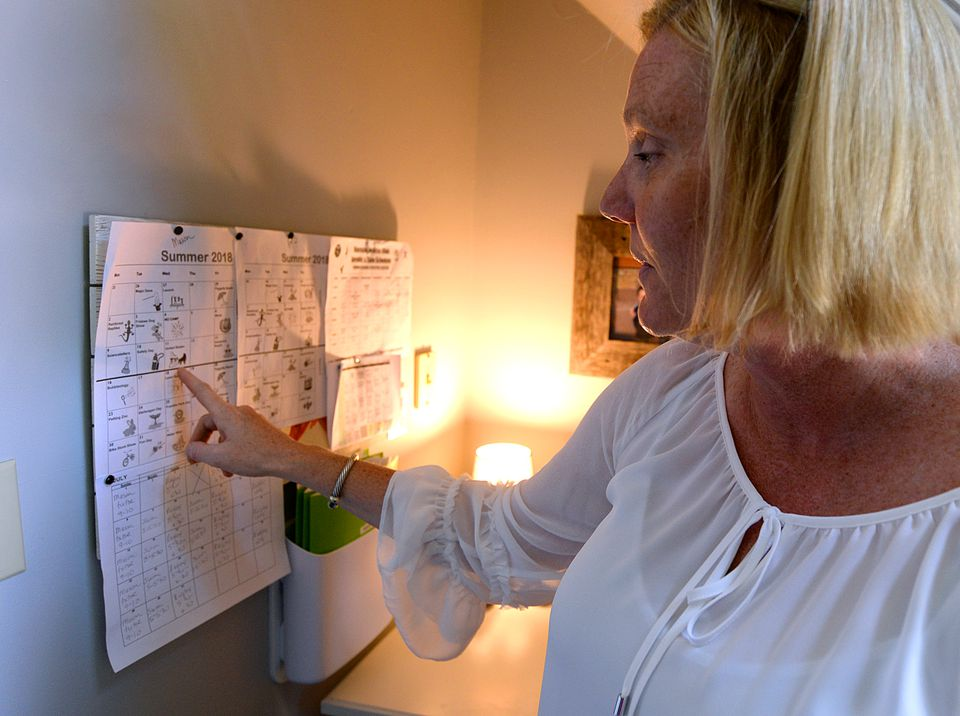 """Lisa Blake, a professional organizer, looks at the schedule of her three sons in the """"Command Central"""" space of her Scituate home."""