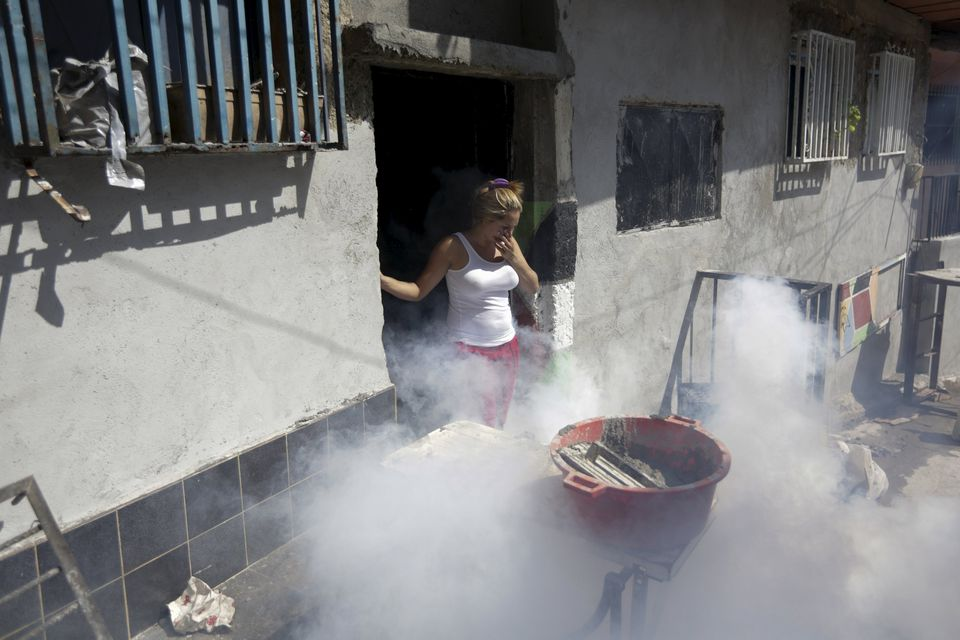 A woman covered her mouth and nose during a fumigation campaign at the Petare slum in Caracas, Venezuela, to help control the spread of the mosquito-borne Zika virus.