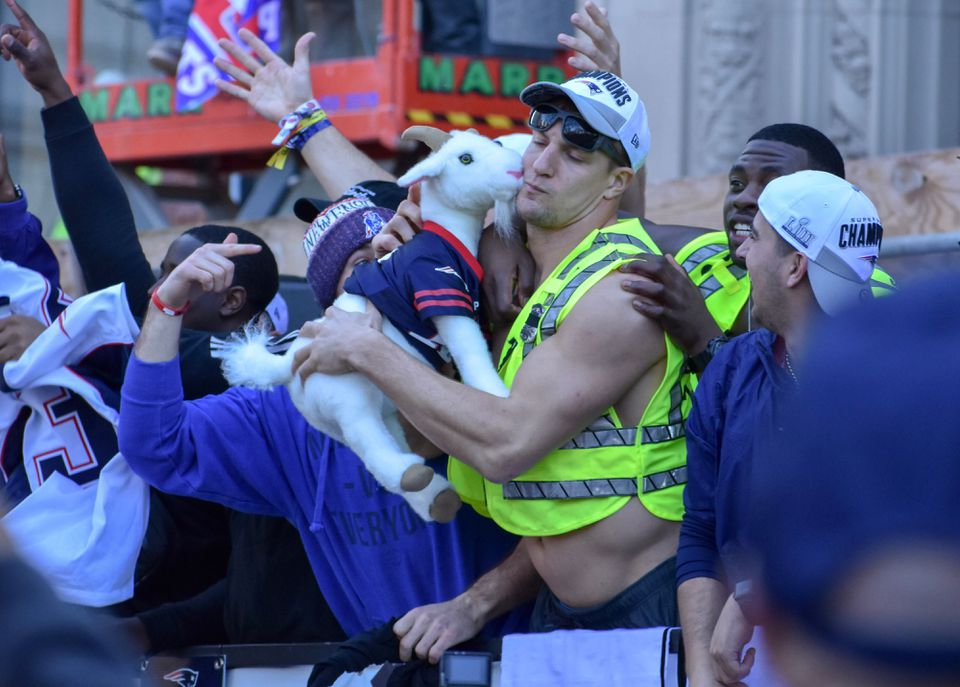 "Rob Gronkowski cuddled with ""Brady,"" a stuffed goat, during the Patriots victory parade."