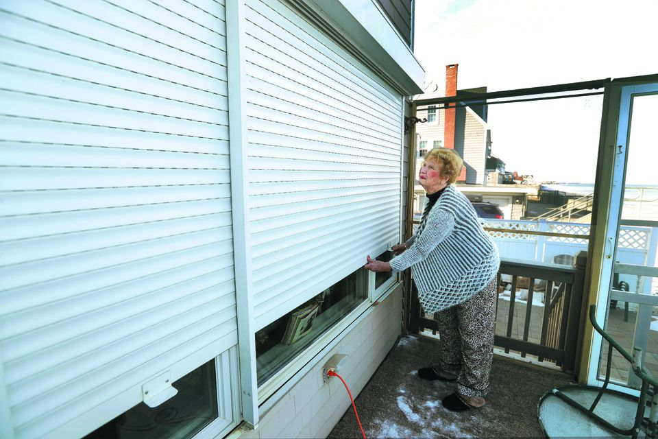 Marshfield resident Glenda Adams lowered protective metal storm curtains over the seaside facing her sunroom in preparation for Thursday's storm and high tides.