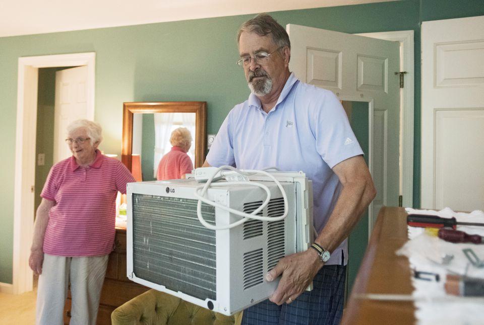 BREWSTER - Nauset Neighbors volunteer Frank Bridges, 66, installs an air conditioning unit for Ann Miller, 79, Tuesday, July 3, 2018.