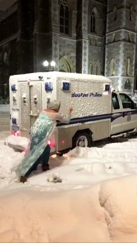 Jason Triplett, dressed in an Elsa costume, pushed a Boston police wagon that was stuck in the snow Tuesday night.