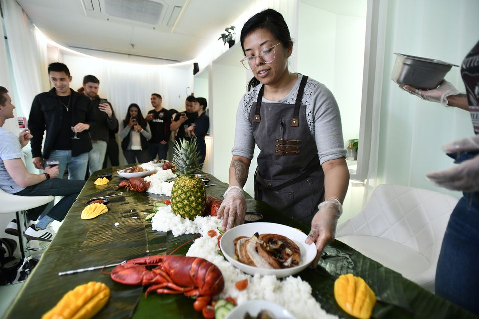 Chef Ellie Tiglao prepares a kamayan table, with platters of food laid out on banana leaves.