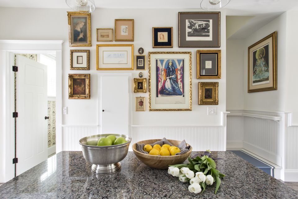 A gallery wall in the kitchen displays a variety of multi-era prints.