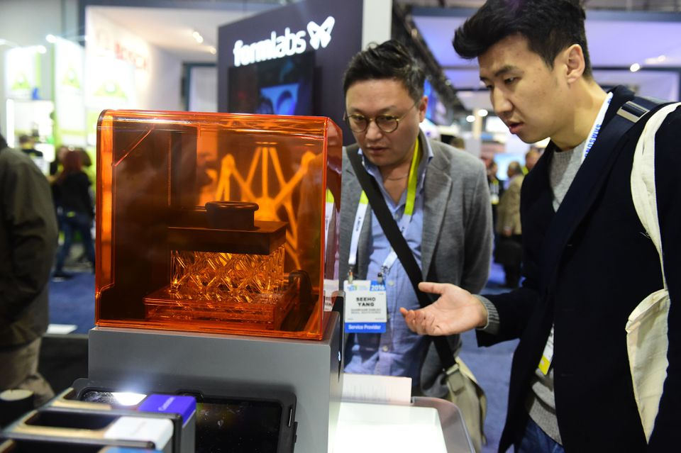 Attendees look at the Form 3-D desktop printer made by Formlabs, at a conference in Las Vegas .