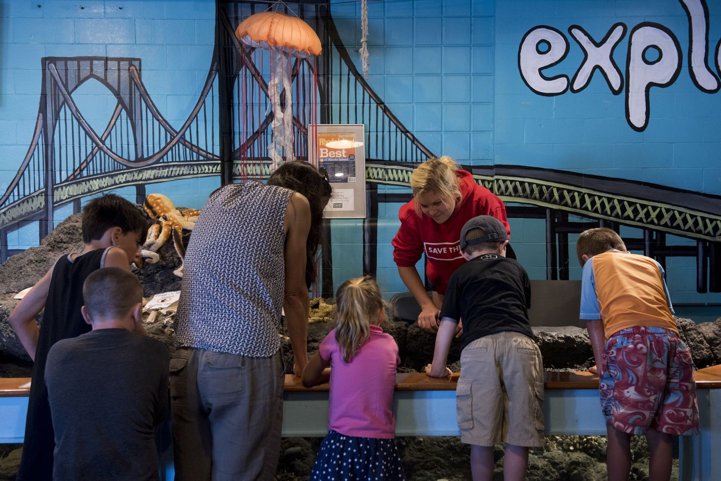 Kate Hoey, a summer intern at Save the Bay Exploration Center & Aquarium, shows children crabs and starfish.