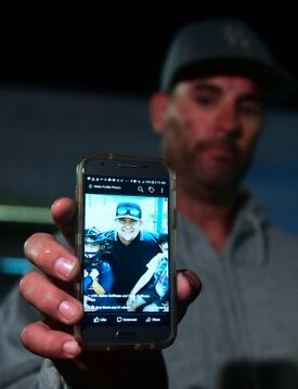 Jason Coffman displayed a photo of his son, Cody, who died in the shooting.