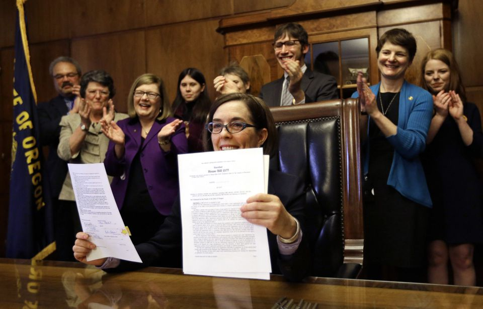 Oregon Governor Kate Brown held up an automatic voter registration bill after signing it on Monday in Salem, Ore.