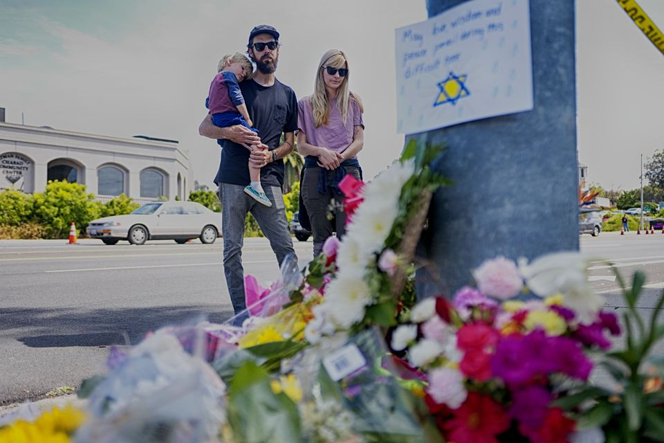 Mourners Troy and Katie McKinney and their son Wynn looked at a makeshift memorial placed outside the Chabad of Poway Synagogue in Poway, Calif.