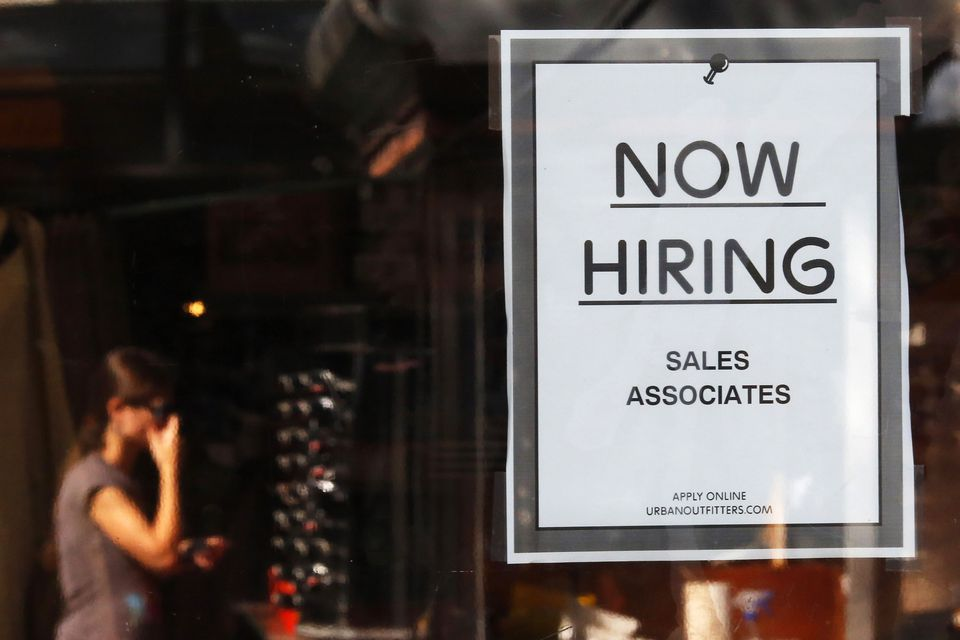 """A """"Now Hiring"""" sign hangs on the door to the Urban Outfitters store at Quincy Market in Boston."""