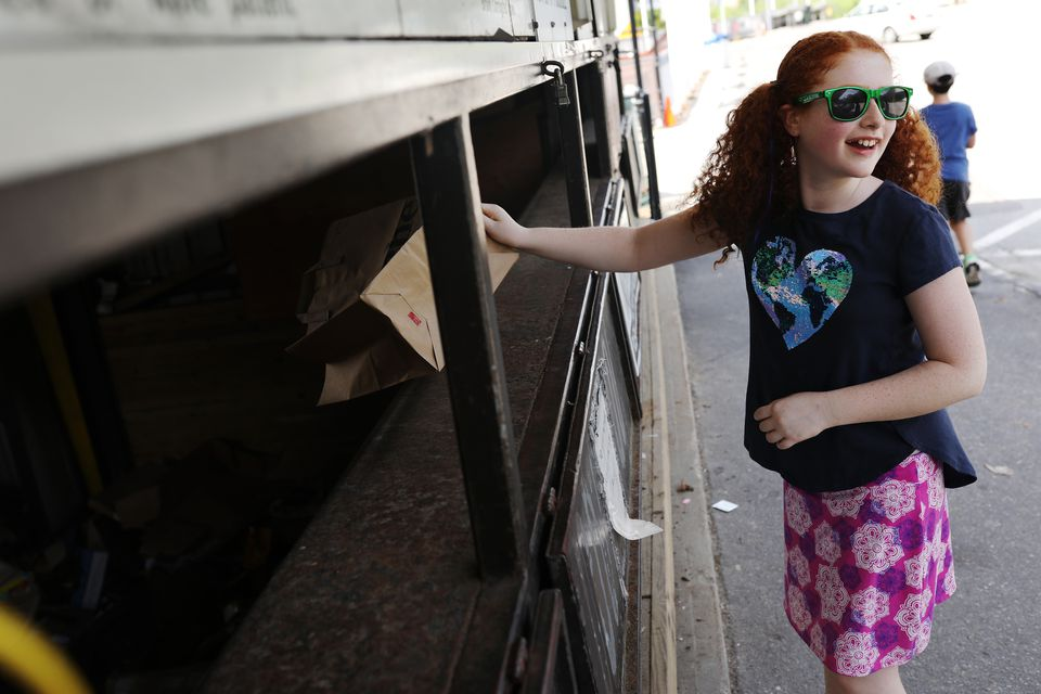 Leah Wechsler, 11, disposed of her family's recycling at the Wellesley Recycling and Disposal Facility.