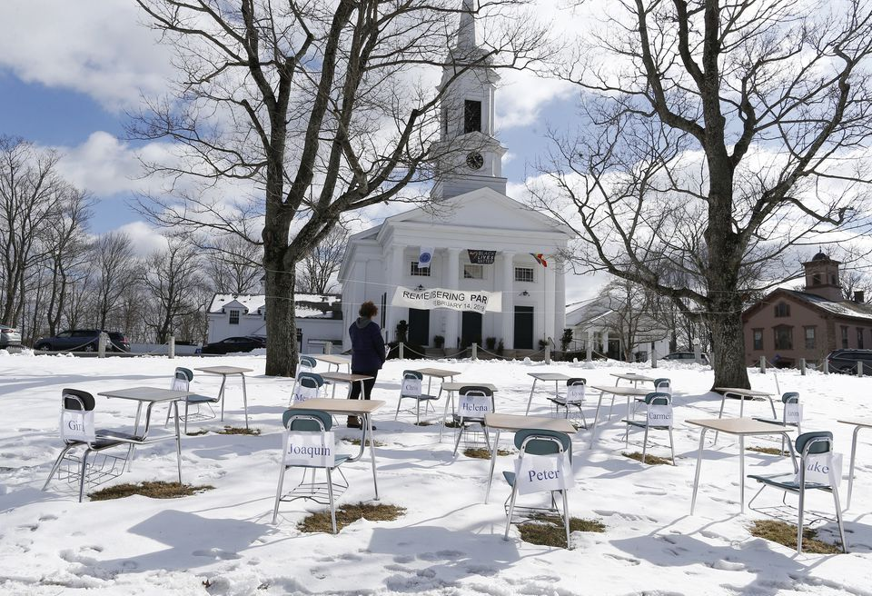 Michele Proulx stopped to pay her respects at the 17 empty desks outside of the Unitarian Universalist Church in Sherborn to mark the one year anniversary of the Parkland school shooting.