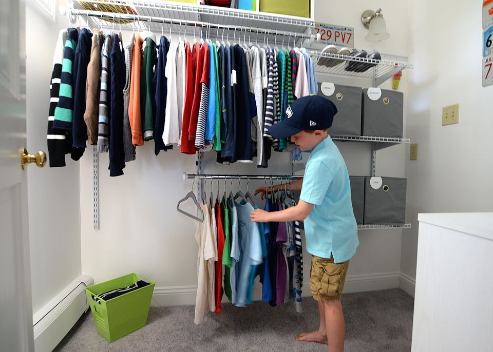 Hunter Maldonis, 8, looks at his shirts in the well-organized closet of his Scituate home.