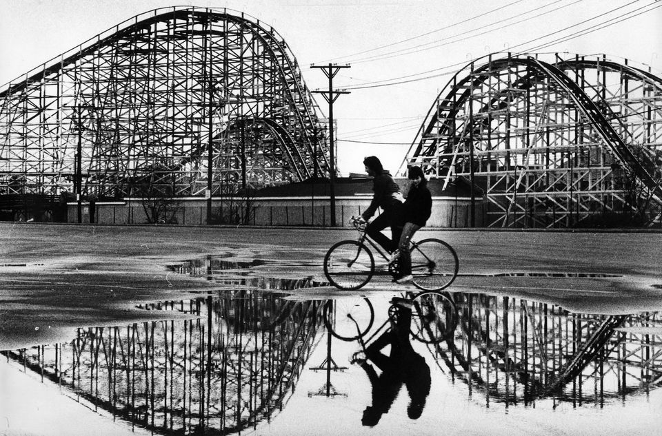 Kelley McLaughlin, 13, and Ann Nigro, 14, of Hull, rode past the Giant Coaster at Paragon Park in Hull on their way home from school on March 24, 1984.