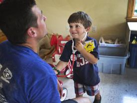 Toby, a 3-year-old at Camp Sunshine, played doctor with a Navy SEAL.