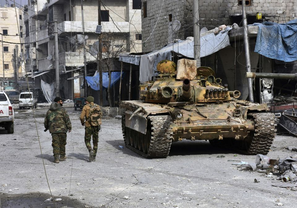 Two Syrian soldiers passed by a tank in a neighborhood of eastern Aleppo where government forces have captured wide areas Monday.